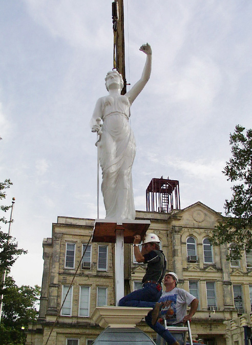 themis statue lifted by crane milam county texas